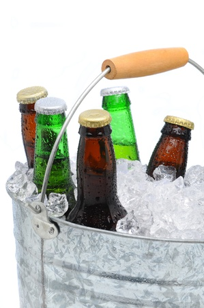 Close-up van een emmer gevuld met ijsblokjes en een assortiment bierflessen op een witte achtergrond.