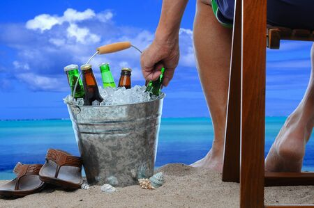 sandals: Close up of a man sitting in a wooden chair at the beach reaching into a bucket filled with ice and beer bottles.