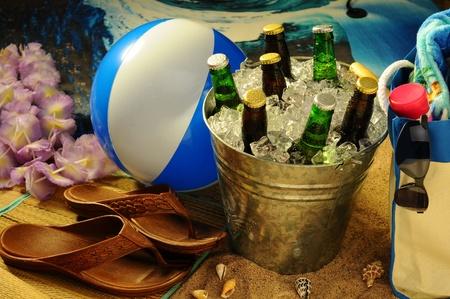 Strandstilleven met warm middagzonlicht. Strandbal, tote, lotion, sandalen, zonnebril en lei omringen een emmer met diverse bierflessen op ijs. Stockfoto