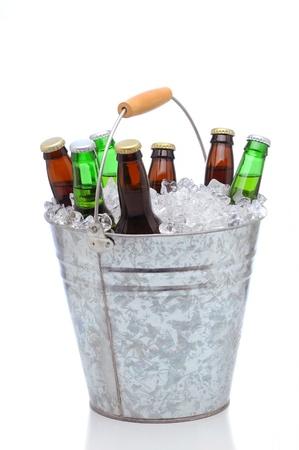 Geassorteerde bierflesjes in een emmer ijs geïsoleerd op een witte achtergrond. Verticale indeling met reflectie.
