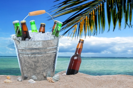 Assorted beer bottles in a bucket of ice in the sand on a tropical beach. One beer bottle without a cap is by itself stuck in the sand next to the pail. photo