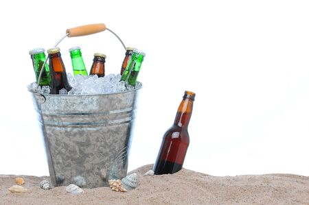 pilsner: Assorted beer bottles in a bucket of ice in the sand isolated on white. One beer bottle without a cap is by itself stuck in the sand next to the pail.