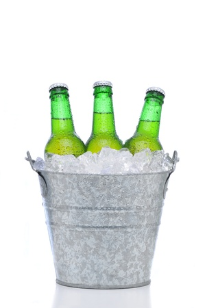 Three green beer bottles in a bucket of ice isolated on a white background. Vertical format with reflection. Bottles and pail have condensation.