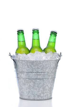 Tres botellas de cerveza verde en un cubo de hielo aislado en un fondo blanco. Formato vertical con la reflexión. Botellas y cubo tienen condensación.