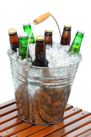 Beer Bucket filled with assorted bottles and ice cubes on teak table in front of a white background. photo