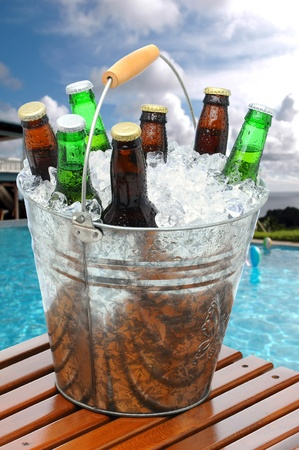 Close up of a beer bucket on poolside teak table. Swimming pool with beach balls and house in background. Cloudy blue sky and ocean in far background.