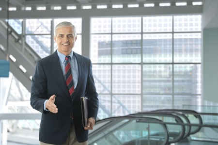 blazer: Smiling middle aged businessman standing in the lobby of a modern office building. Man is wearing a blue blazer and khaki pants with hand extended to shake. Horizontal Format.