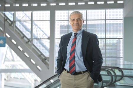 50 yrs: Smiling middle aged businessman standing in the lobby of a modern office building. Man is wearing a blue blazer and khaki pants with hands in his pockets. Horizontal Format.