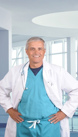 50 yrs: Close up portrait of a smiling middle aged doctor in scrubs with stethoscope around his neck. Vertical format in modern medical facility.