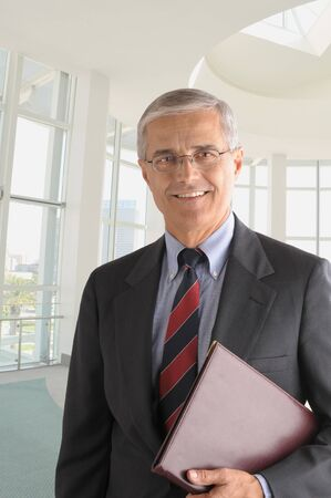 Middle aged businessman in modern office building with leather folder under his arm  photo