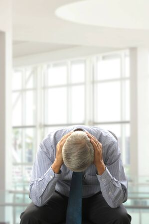 50 yrs: Seated Middle Aged Businessman Doubled Over with His Head in Hands in a modern business office. Vertical Format.