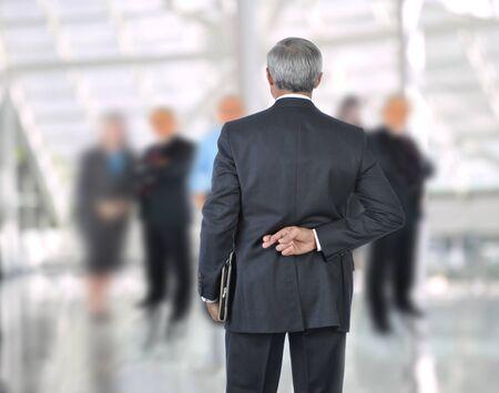deceptive: Permanent zaken man met vingers gekruist achter de rug. Hij staat voor een out of focus groep mensen. Horizontale indeling.