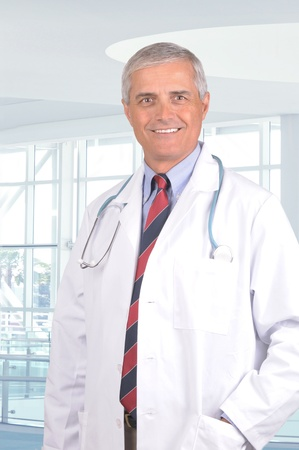 Smiling Middle Aged Male Doctor in Lab Coat with Stethoscope standing in a modern medical facility. photo