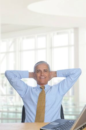 Businessman sitting at his desk in a modern office building with hands behind his head. Vertical Format Stock Photo - 8736297