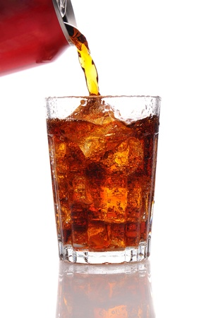 Cola pouring from a can into a glass filled with Ice. Vertical format isolated over a white background.  photo