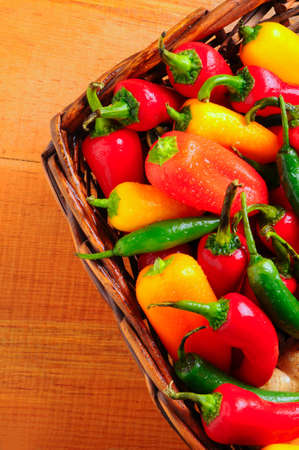 Closeup of assorted peppers and chilies in a wicker basket on a rustic wood table. photo