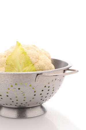 head of cauliflower: Closeup of a head of Garden Fresh Cauliflower in Colander on a white surface misted with water drops. Vertical format.