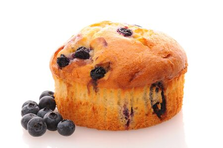 blueberry muffin: Closeup of a Blueberry Muffin on a white plate with loose berries on a rustic wooden table. Horizontal format.