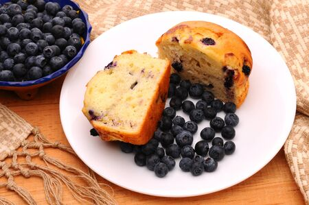 Delicious Blueberry Muffin cut in half with loose berries on a white plate on a rustic wooden table. Vertical format with shallow depth of field. Stock Photo - 9207537
