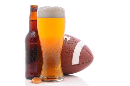 American Football achter een fles en glas bier met condensatie. Horizontale indeling op een witte achtergrond met reflectie.  Stockfoto