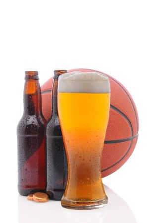 Two open beer bottles and a glass with a basketball on a white background.  Vertical format from a low angle with reflection.  Stock Photo - 9207500