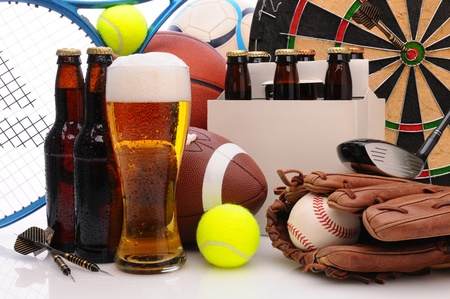 Six pack of beer and frothy glass surrounded by sports equipment. Horizontal Format Filling the frame. Sports represented include, football, basketball, soccer, darts, baseball, tennis and golf. photo