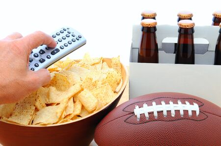 Closeup of a mans hand holding a TV remote with a bowl of chips six pack of beer and football isolated on white. Horizontal Format.