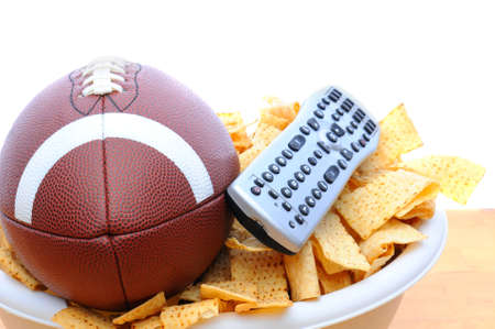 snack: Closeup of a TV remote with a bowl of chips and football isolated on white. Horizontal Format.
