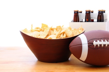 6 pack beer: Chips, football and Six Pack of Beer on a table with a white background. Horizontal format. Stock Photo
