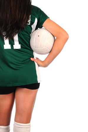 arms akimbo: Female Volleyball player seen from behind holding a ball in the crook of her arm and held against her body. She is set to one side of the frame only showing knees to shoulder.