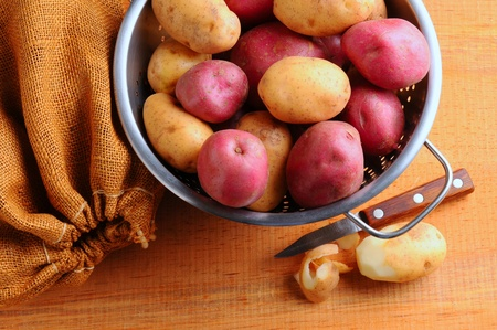 paring knife: Potatoes in Colander with Burlap Sack and Paring Knife. Horizontal format shot from high angle. Stock Photo