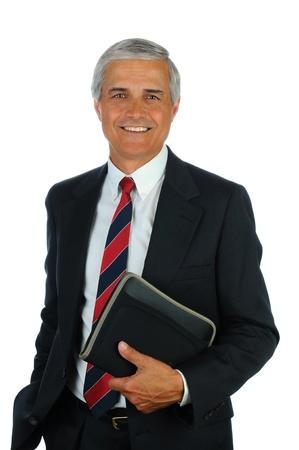 彼のポケットに片手で小さなバインダーを保持笑みを浮かべて中間の老化させたビジネス男の肖像画。白で隔離される垂直方向の形式です。