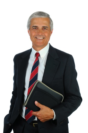 Portrait of a smiling middle aged business man holding a small binder with one hand in his pocket. Vertical format isolated on white.