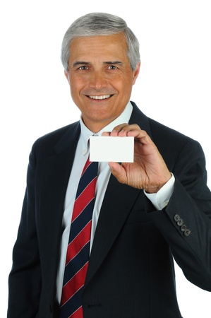 businesscard: Portrait of a smiling middle aged business man holding a blank business card in front of his body. Vertical format isolated on white.
