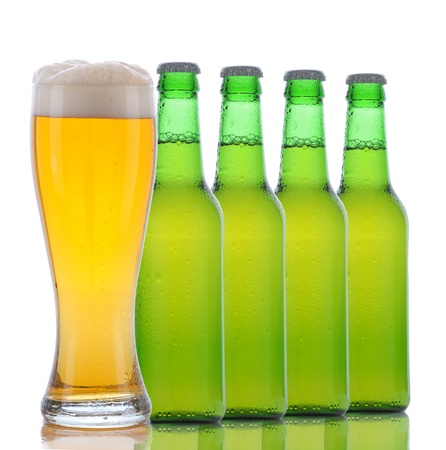Four Green Beer Bottles and a Full Glass of ale on a white background. Square format with bottles arranged in a line behind the glass. Stock Photo - 9419673
