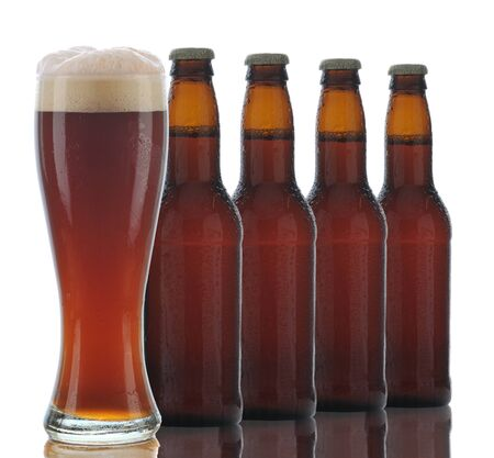Four Brown Beer Bottles and a Full Glass of dark ale on a white background. Stock Photo - 9419674