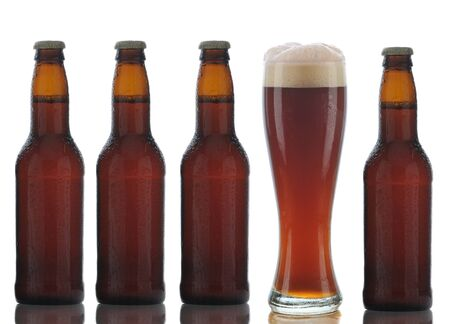 ale: Four Brown Beer Bottles and a Full Glass of dark ale on a white background.
