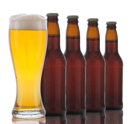 Four Brown Beer Bottles and a Full Glass of ale on a white background. Glass is in front of bottle.