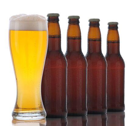 Vier bruine bierflessen en een vol glas bier op een witte achtergrond. Glas staat voor een fles. Stockfoto