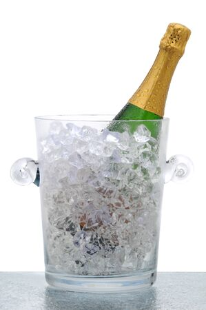 Champagne bottle in a crystal bucket filled with ice. Vertical format isolated on white,