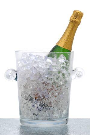 Botella de Champagne en un cubo de cristal lleno de hielo. Formato vertical aislado en blanco,