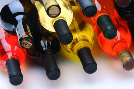 Closeup of a group of assorted wine bottles laying on their side.