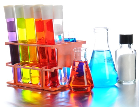 Closeup of scientific labortory equipment on shiny metal surface. Test tubes, beakers and vials filled with colorful liquids on a white background.