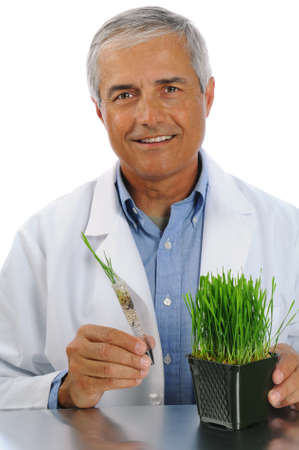 Smiling scientist holding a test tube plant with plant in container on table. Vertical format isolated over white.