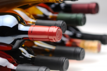 Closeup of several assorted wine bottles laying on their side. Horizontal format with selective focus.