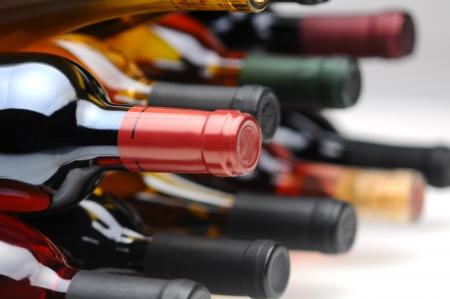 white wine bottle: Detalle de varios surtidos botellas de vino de su lado. Formato horizontal con enfoque selectivo. Foto de archivo