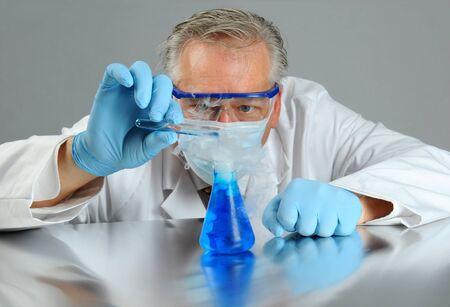 vaso de precipitado: Detalle de un cient�fico loco verter un l�quido de un tubo de ensayo en un vaso de precipitados que est� emitiendo humo. Formato horizontal.