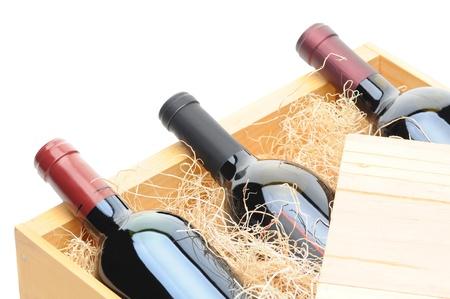 Close-up van drie Cabernet Sauvignon wijn flessen aan hun zijde in een houten krat. Krat deksel wordt getrokken gedeeltelijk terug flessen belichten en verpakking excelsior. Horizontale indeling geïsoleerd op wit.