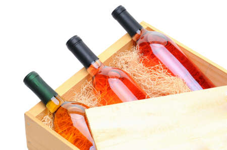 excelsior: Closeup of three blush wine bottles on their side in a wooden crate. Crate lid is pulled partially back exposing the bottles and packing excelsior. Horizontal format isolated on white.