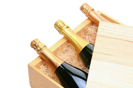 Closeup of three Champagne bottles on their side in a wooden crate. Crate lid is pulled partially back exposing the bottles and packing excelsior. Horizontal format isolated on white.